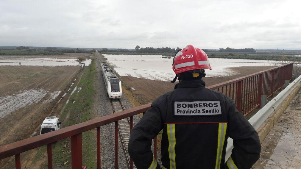 Un bombero mira el tren descarrilado desde un puente