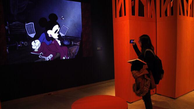 Una visitante fotografía una proyección de Mickey Mouse en la exposición 'Disney. El arte de contar historias'.