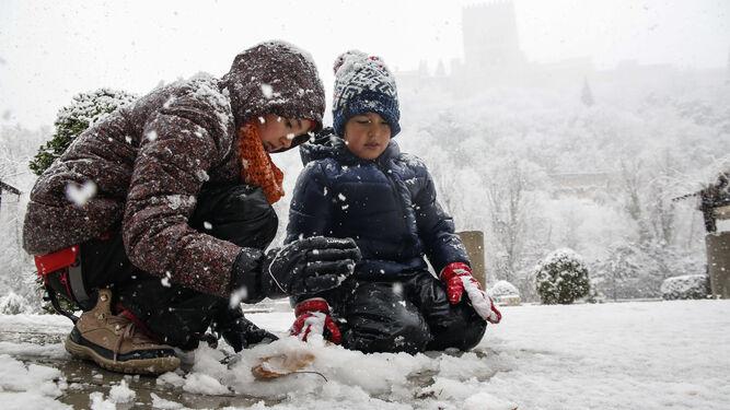 Dos niños juegan con la nieve en Granada.