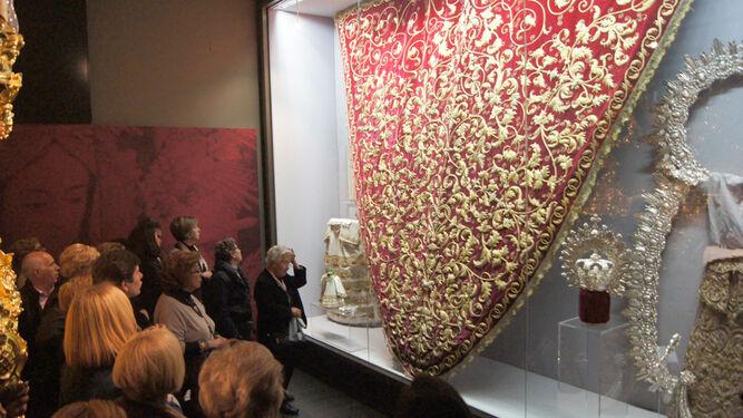 Varios visitantes contemplan una de las vitrinas del museo
