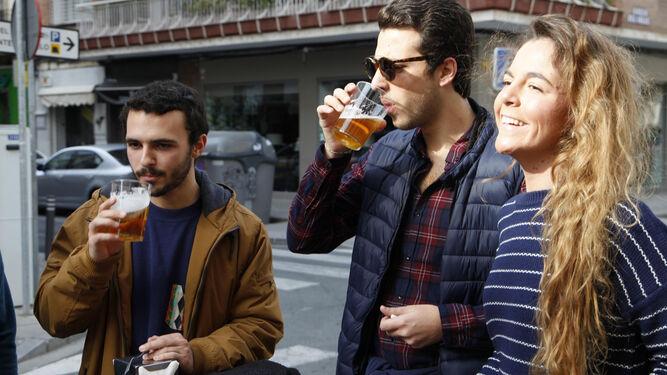 El suave invierno sevillano no impide a los sevillanos disfrutar de una buena cerveza en la calle, como ayer hacían unos jóvenes.