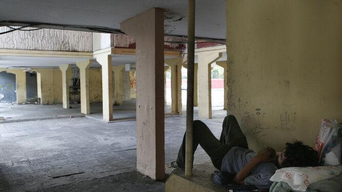Un heroinómano descansa sobre una cama improvisada en las Tres Mil Viviendas.
