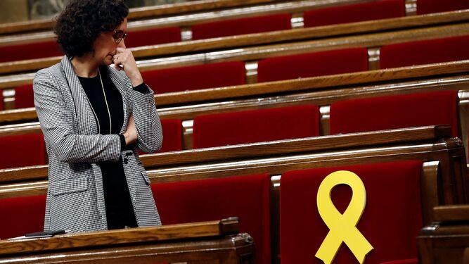 Marta Rovira, secretaria general de ERC, observa ayer el escaño del presidente de su formación, Oriol Junqueras, adornado con un lazo amarillo en el 'Parlament'.
