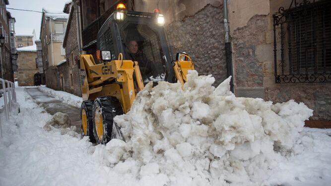 Un operario ayudado por una máquina retira la nieve en una calle