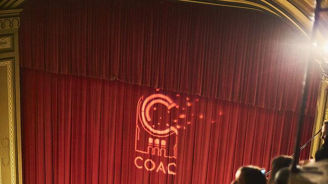 El telón del Gran Teatro Falla con el logo del COAC sobreimpresionado.