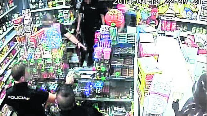 DINERO EN EL MOSTRADOR. Uno de los agentes coloca en el mostrador de la tienda el dinero que había en una caja, mezclado con tabaco, para su recuento posterior.
