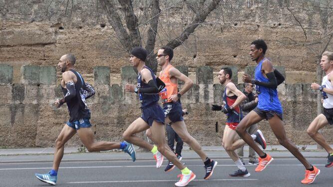 Corredores durante un tramo de la carrera ante la muralla de la Macarena