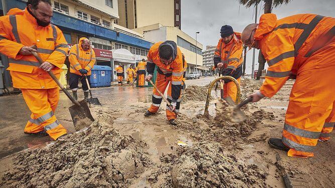 Un grupo de operarios trabajando en la playa de Cádiz.