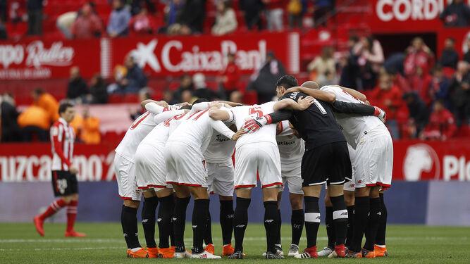 El once inicial del Sevilla el pasado sábado ante el Athletic se conjura en una piña antes de comenzar el partido.