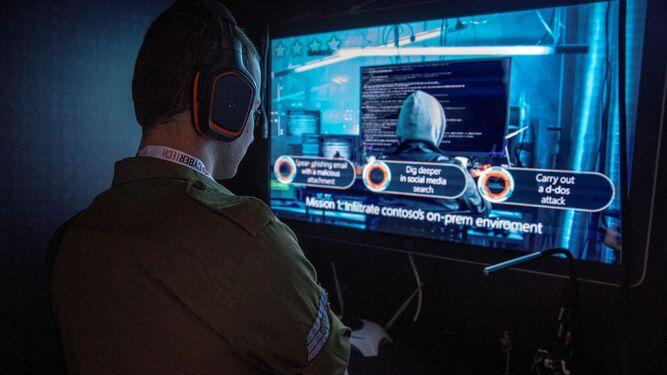 Un soldado observa una presentación sobre hackeo y ciberseguridad.