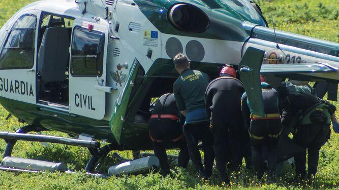 Agentes de la Guardia Civil introducen el cuerpo del cabo Diego Díaz en un helicóptero.