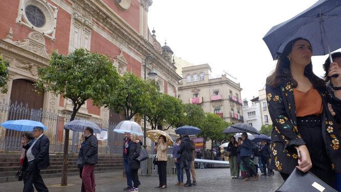 Personas aguardan bajo la lluvia para entrar en el Salvador.