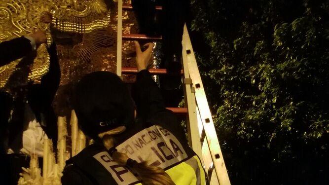 Una agente de la Policía Nacional intenta arreglar el palio.