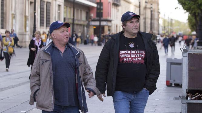 Dos aficionados del Bayern Múnich, perfectamente identificados por su camiseta y su gorra, pasean por la Avenida de la Constitución.