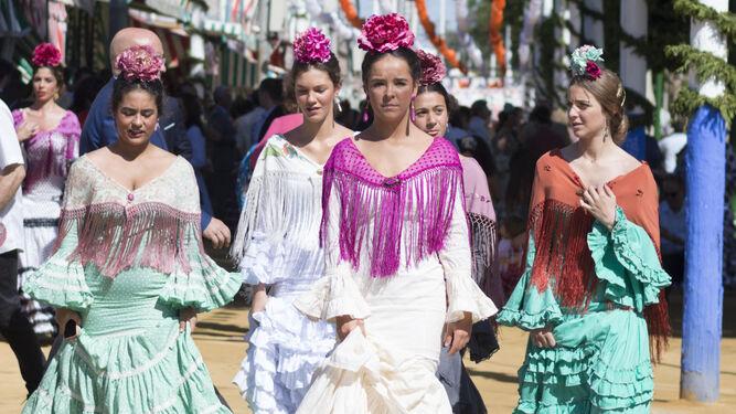 d3d8671674ad5 Varias jóvenes pasean por el Real de la Feria de Sevilla vestidas de  flamenca.