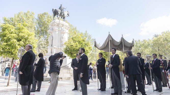 El Santísimo, bajo palio, atraviesa la Plaza Nueva. La estatua de San Fernando, el rey que trajo de nuevo el cristianismo a Sevilla, lo observa todo.