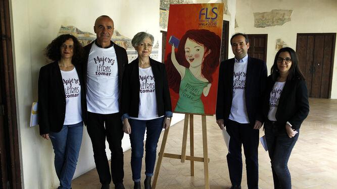 Los organizadores de la Feria ante el cartel de esta edición, firmado por Irene Mala.