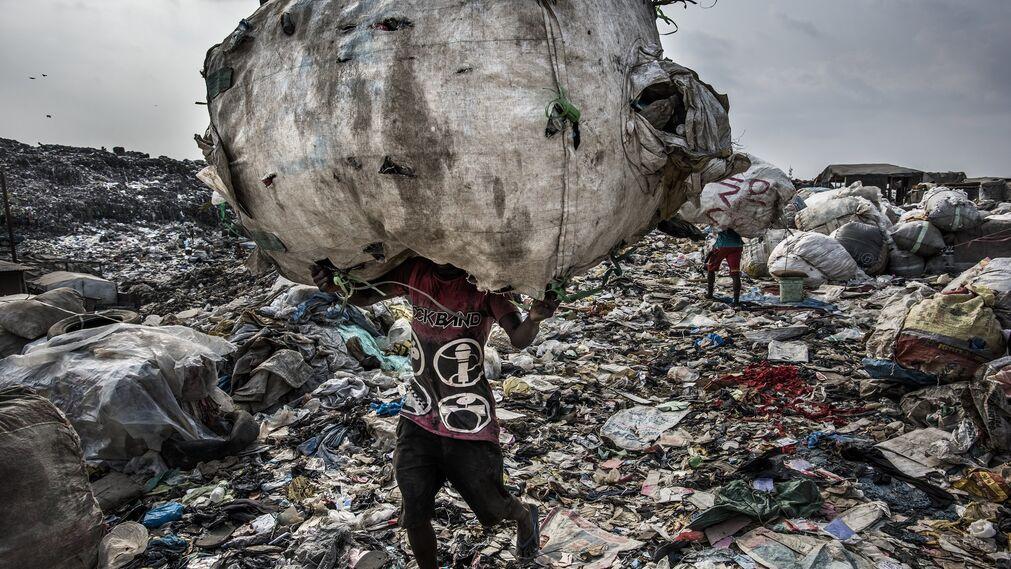 La imagen captada por el fotógrafo Kadir van Lohuizen, ganador del 1er premio de la categoría 'Environment - Stories'. Se ve a  un hombre mientras carga un enorme lomo de botellas recogidas para su reciclaje en el vertedero de Olusosun en Lagos, Nigeria, el 21 de enero de 2017