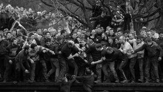 Imagen captada por el fotógrafo Oliver Scarff, ganador del primer premio de la categoría 'Sports - Singles'. Muestra a los miembros de equipos contrarios, los Up'ards y Down'ards, luchando por el balón durante el histórico y anual partido de fútbol Royal Shrovetide en Ashbourne, Derbyshire (Reino Unido), el 28 de febrero de 2017.