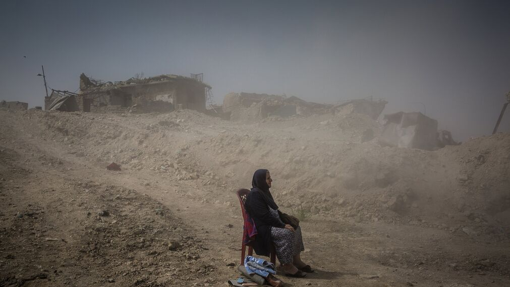 Foto de Ivor Prickett, ganador del primer premio de la categoría 'General News - Stories'. Sale Nadhira Aziz mientras observa a los trabajadores de la Defensa Civil iraquí sacando los cuerpos de su hermana y sobrina de su casa en la Ciudad Vieja, donde fueron asesinadas por un ataque aéreo en Mosul, Irak, el 16 de septiembre de 2017. Al final de la batalla por la segunda ciudad más grande de Iraq, más de 9.000 civiles fueron asesinados.