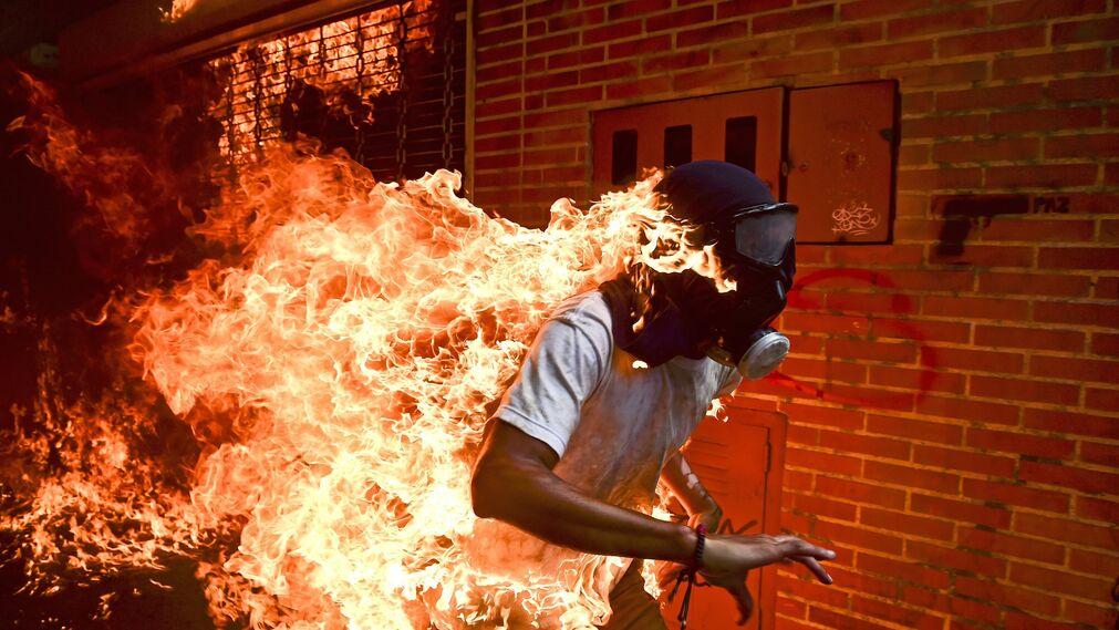 """Foto de  Ronaldo Schemidt, ganador del premio """"Fotografía del año 2018"""" y del 1er premio de la categoría 'Spots - Singles'. Se ve al manifestante José Víctor Salazar Balza (28) en llamas durante los enfrentamientos con la policía antidisturbios durante una protesta contra el presidente venezolano Nicolás Maduro en Caracas (Venezuela) el 3 de mayo de 2017"""
