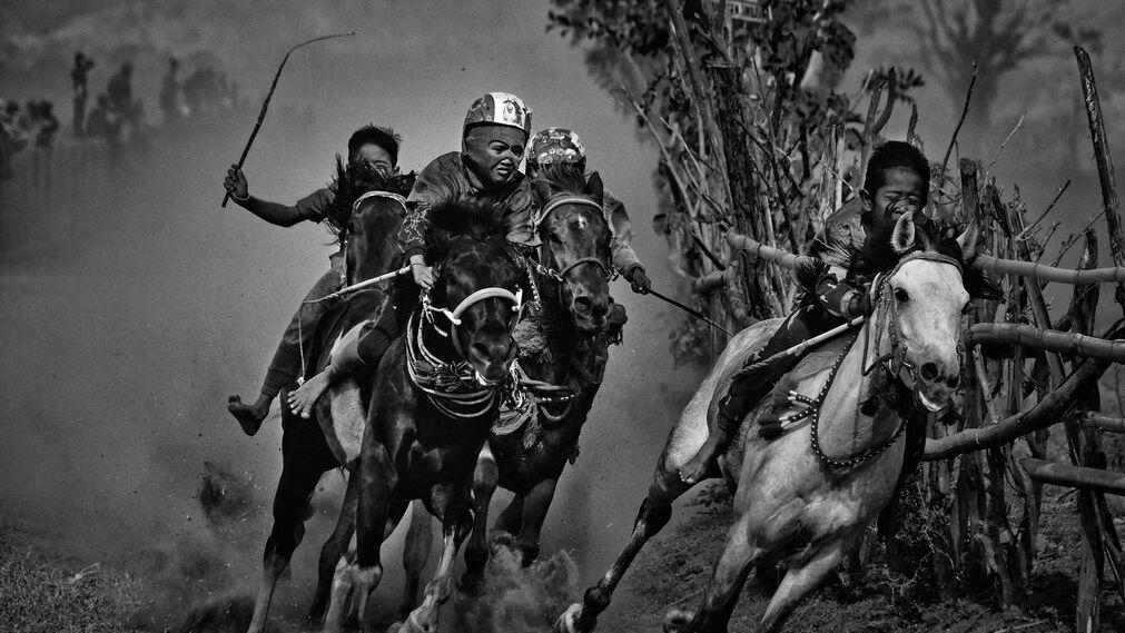 La imagen captada por el fotógrafo Alain Schroeder, ganador del 1er premio de la categoría 'Sports - Stories'. La foto muestra a jóvenes jinetes que compiten en una carrera de caballos de Maen Jaran, en la isla de Sumbawa, Indonesia, el 17 de septiembre de 2017.
