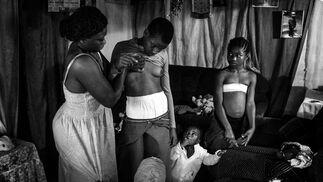 Foto de  Veronica, de 28 años, mientras masaje el pecho de su hija de 10 años Michelle, en compañía de sus otras hijas en Bafoussam, Camerún, el 7 de noviembre de 2016.  Hecha por Heba Khamis, es la  ganadora del 1er premio de la categoría 'Contemporary Issues'