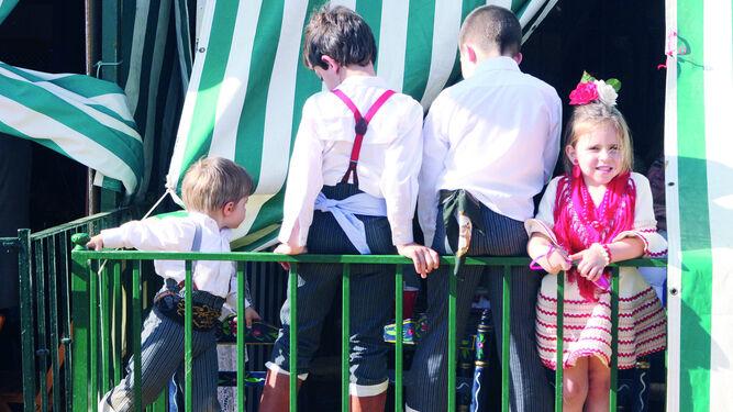 1. Los niños aprovechan la Feria para jugar en las casetas y con el albero.  2. Las chapas de La Tita Ana tienen mensajes con humor para localizar a los pequeños.            3. Policía local, Bomberos y Protección Civil repartirán pulseras identificativas que facilitan la localización de los menores que se pierdan.