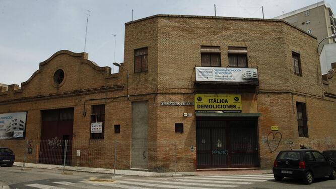 Dos carteles anuncian la inminente demolición de las naves y los nuevos pisos.
