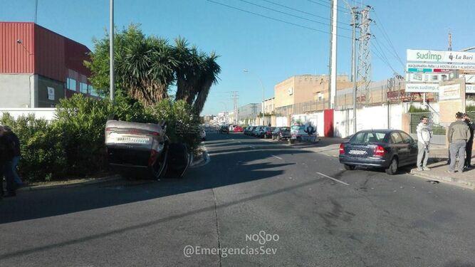 El coche volcado en el accidente al fondo.