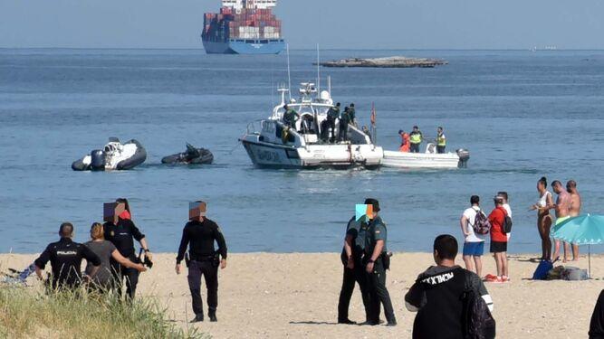 Policía Nacional y Guardia Civil trabajan en la playa. Al fondo, las embarcaciones implicadas en los hechos.