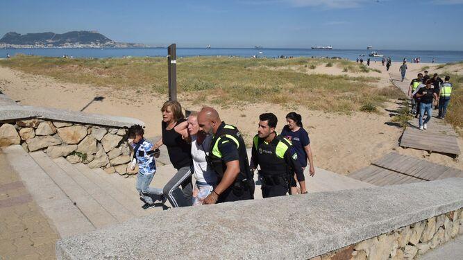 La Policía acompaña a los familiares del pequeño mientras abandonan la playa.