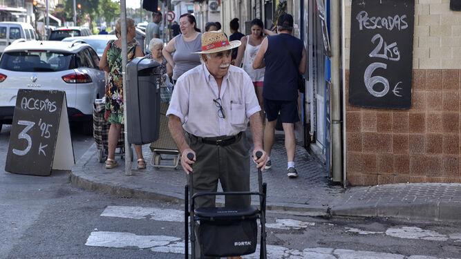 Un hombre camina con ayuda de un andador en Torreblanca.