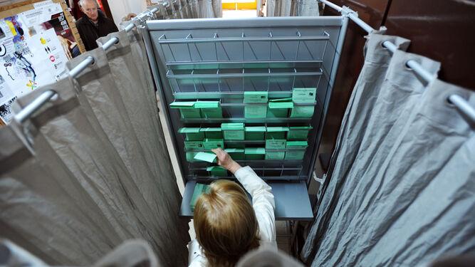 Una imagen de archivo de papeletas con distintas candidaturas colocadas en una cabina, en un colegio electoral.