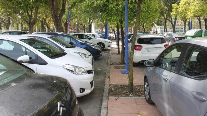 Coches aparcados que invaden las aceras de la Cartuja. Hace falta regular el aparcamiento.