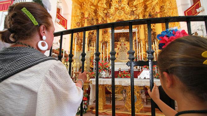 Dos mujeres tras la reja, admiran a la Virgen.