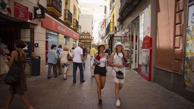 Turistas en la calle Sierpes, copada por franquicias y firmas nacionales.