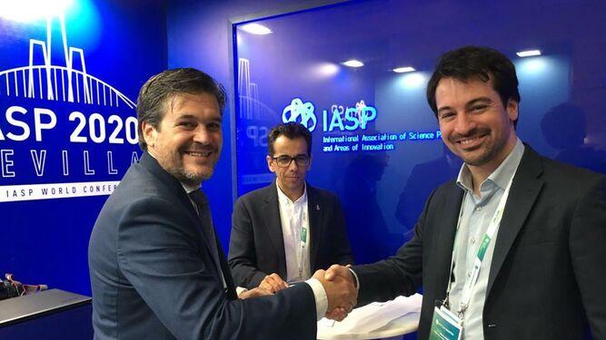 Luis Pérez, a la izquierda, estrecha la mano a Iván Alejandro Diamint, responsable del Parque de Buenos Aires, en presencia de Manuel Ortigosa Brun, secretario de Empresa, Innovación y Emprendimiento de la Junta de Andalucía.