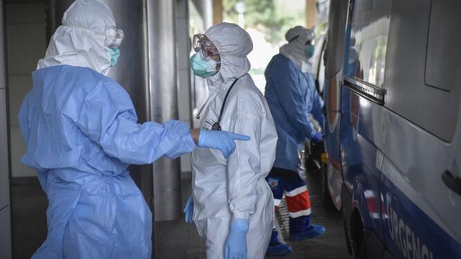 Dos sanitarios equipados con equipos de protección individual a las puertas de las Urgencias del Virgen Macarena.
