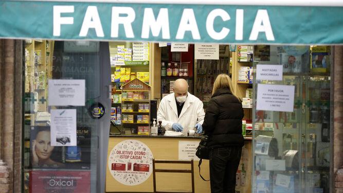 Una farmacia de Sevilla con varios carteles que indican que no hay mascarillas.