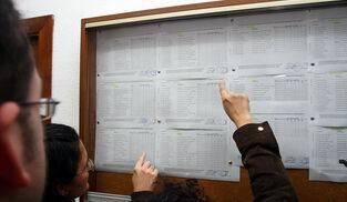 Padres comprueban las listas provisionales de niños admitidos en un colegio concertado.