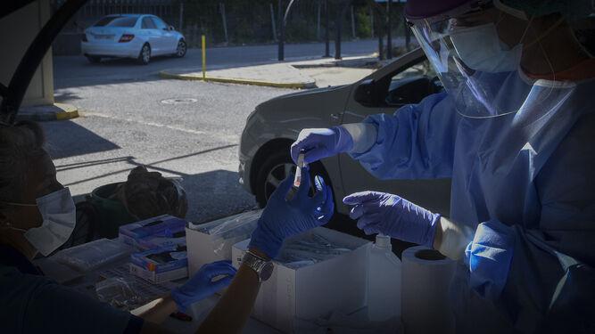 Una enfermera entrega una muestra para su clasificación en el autocovid del distrito sanitario Sevilla.