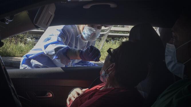 Una enfermera toma muestras a una posible afectada en el autocovid.