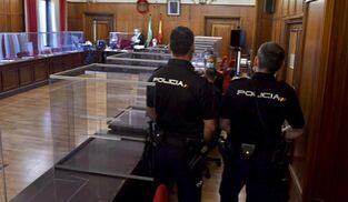 El acusado, entre su abogada y dos policías nacionales antes del incidido del juicio.