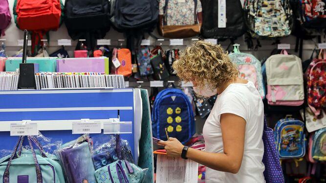 Una madre busca el material escolar para el curso que viene.