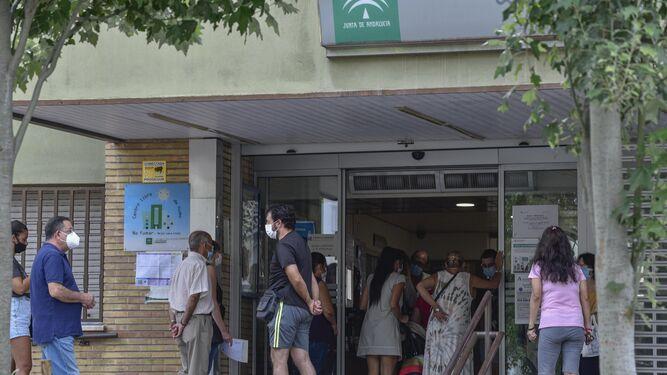 Varias personas hacen cola para poder acceder al interior del centro de salud de El Greco.