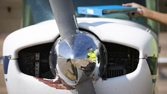 Un guardia reflejado en la hélice de una avioneta.