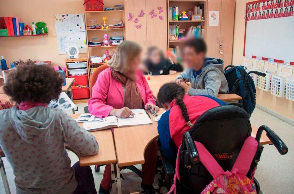 Una maestra atiende a varios alumnos del Colegio Arco Auxilia.