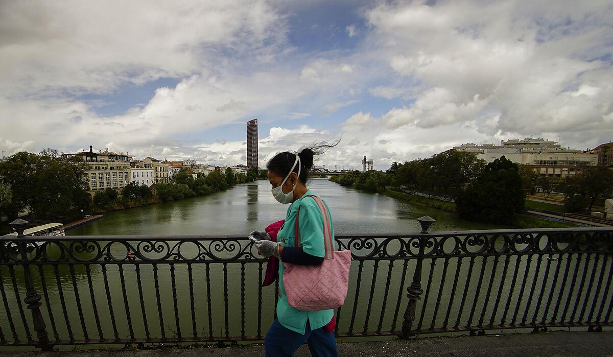 Una mujer mira el móvil al cruzar el Puente de Triana.
