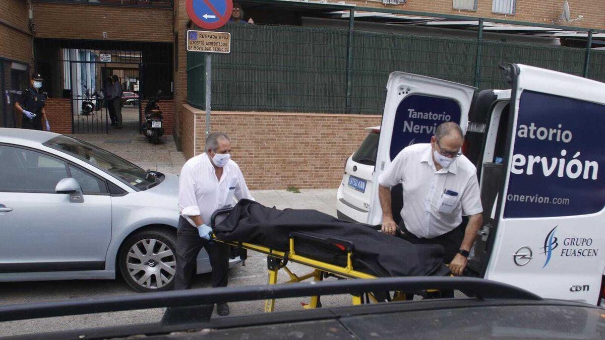 Momento en el que los servicios funerarios sacan el cadáver del domicilio de la víctima, la mañana de este jueves.